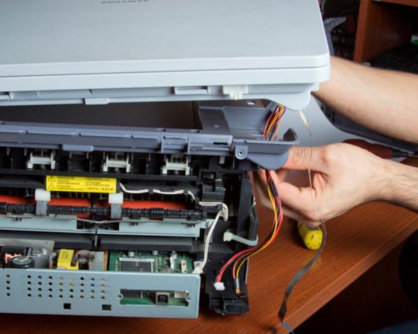 men's hands repairing laser printer